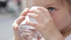 Close-up of a little cute girl drinking pure water from a glass. Outdoor stock video footage