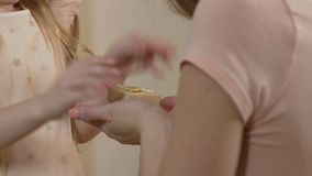 Close-up of little daughter giving a gift to mother, family values, relations. Stock footage stock footage