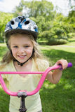 Close-up of a little girl on a bicycle at park Stock Images