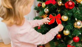 Close up of little girl decorating christmas tree Royalty Free Stock Photos