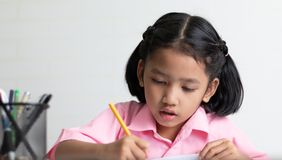Close up the little girl is doing homework intently royalty free stock images