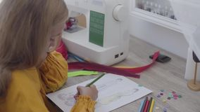 Close-up of little girl drawing clothing designs sitting at the table in the foreground while her mother sewing clothes