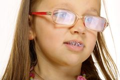 Close up little girl in glasses doing fun saliva bubbles Stock Image