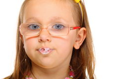 Close up little girl in glasses doing fun saliva bubbles Royalty Free Stock Images