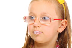 Close up little girl in glasses doing fun saliva bubbles Stock Photo