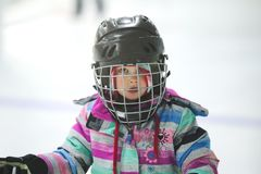 Close up of little girl in a hockey helmet. Close up of a five year old girls` face under a black hockey helmet with a snow cap partially covering one eye Royalty Free Stock Image