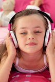 Close-up of a little girl listening musc Stock Images