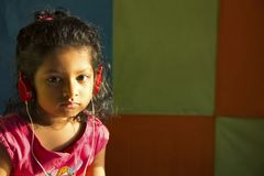 Close-up of little girl listening to music with red colored headphones, Pune, India royalty free stock photography