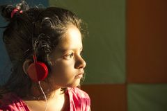 Close-up of little girl listening to music with red colored headphones in sunlight, Pune, India stock photos