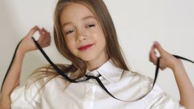 Close-up of little girl in long flowing hair posing in a room with a white wall. Close-up portrait of a cute little girl with big brown eyes and long hair posing stock video
