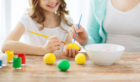 Close up of little girl and mother coloring eggs Stock Image