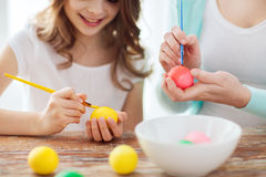 Close up of little girl and mother coloring eggs. Easter, family, holiday and child concept - close up of little girl and mother coloring eggs for easter Royalty Free Stock Image