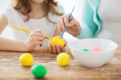 Close up of little girl and mother coloring eggs Royalty Free Stock Photos