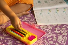 Close up little girl picking up sketchpen from compass box for coloring, Pune, India stock photography