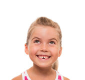 Close up of little girl's face looking straight up and smiling. There is something interesting above Stock Photography