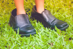Close up little girl`s foot wear black business shoes and standing on green grass. Stock Photography
