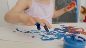 Close-up of a little girl`s hand, drawing on paper with bright colors, dipping her fingers in cans of paint. Close-up of the hand of a little girl sitting at a stock video footage