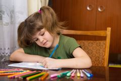 Close up of little girl`s hands drawing by multi-colored pencils royalty free stock images