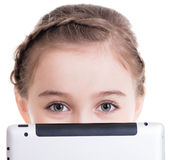 Close-up of little girl sitting with the tablet. Stock Images