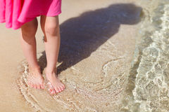 Close up of little girl standing at beach. Close up of a little girl feet on tropical sandy beach Stock Photos