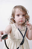 Close-up of a little girl with a stethoscope. Little girl in a dress on a white background with a stethoscope Stock Photos