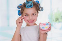 Close up of little girl using make up while wearing hair-rollers and bathrobe in a blurred background.  Stock Image