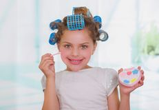 Close up of little girl using make up while wearing hair-rollers and bathrobe in a blurred background.  Royalty Free Stock Images