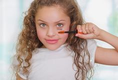 Close up of little girl using wrong an eye mascara in her face in a blurred background.  Stock Photo