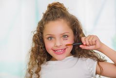Close up of little girl using wrong an eye mascara in her face in a blurred background.  Royalty Free Stock Photo