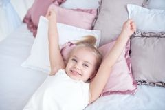 Close-up little girl waking up with stretching arms while awake lying on white bed linen.  Stock Photo