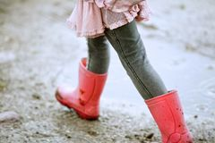 Little Girl Walking Outdoors with Red Boots Stock Images