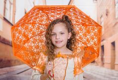 Close up of little girl wearing a beautiful colonial costume and holding an orange umbrella in a blurred background.  Stock Photography