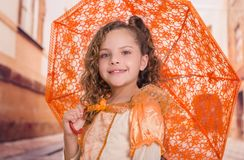 Close up of little girl wearing a beautiful colonial costume and holding an orange umbrella in a blurred background.  Royalty Free Stock Photo