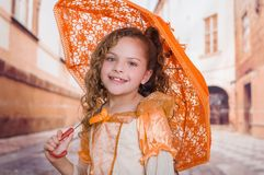 Close up of little girl wearing a beautiful colonial costume and holding an orange umbrella in a blurred background.  Stock Image