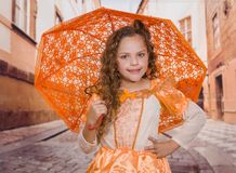 Close up of little girl wearing a beautiful colonial costume and holding an orange umbrella and posing with a hand in. Her waist, in a blurred background Royalty Free Stock Photo