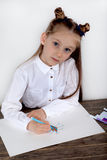 Close up of little girl in white blouse which is focused on drawing. Preschooler is learning how to draw. Kindergarten and school. Family fun stock image