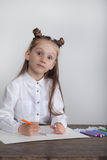 Close up of little girl in white blouse which is focused on drawing. Preschooler is learning how to draw. Kindergarten and school. Royalty Free Stock Photos