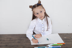 Close up of little girl in white blouse which is focused on drawing. Preschooler is learning how to draw. Kindergarten and school. Royalty Free Stock Image