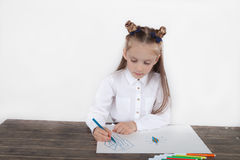 Close up of little girl in white blouse which is focused on drawing. Preschooler is learning how to draw. Kindergarten and school. royalty free stock photo