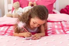 Close-up of a Little girl writing on bed Royalty Free Stock Photos