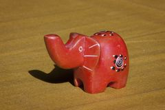 Close up of a little hand made African elephant. Close up of a little hand painted red African figurine of an elephant stock photography