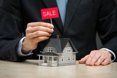 Close up of little home and hand keeping sale tablet stock image