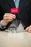 Close up of little house and hand keeping sale tablet Stock Image