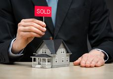 Close up of little house and hand keeping sold tablet Stock Photos