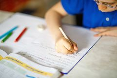 Close-up of little kid boy with glasses at home making homework, writing letters with colorful pens. Little child doing exercise, indoors. Elementary school royalty free stock photography