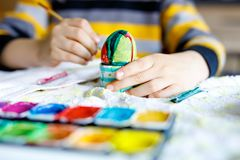 Close-up of little kid hands coloring eggs for Easter holiday. In domestic kitchen, indoors. Child having fun with painting colors and celebrating feast stock photos