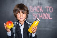 Close-up of little school boy with apple and juice Stock Photo