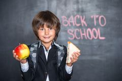 Close-up of little school boy with apple and. Sandwich standing near blackboard with words back to school on it Royalty Free Stock Photos