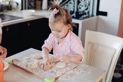 Cute child in flour cooking together with parent at kitchen. Close up of little serious kid sitting on white chair in pink pajama. Lovely daughter helping her stock photography