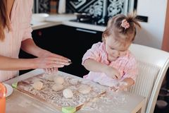 Cute child in flour cooking together with parent at kitchen. Close up of little serious kid sitting on white chair in pink pajama. Lovely daughter helping her royalty free stock images
